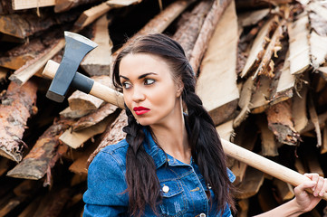 beautiful woman looking away holding an ax in hand