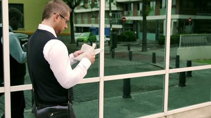 Businessman walking on the street and reading gazette, steadycam
