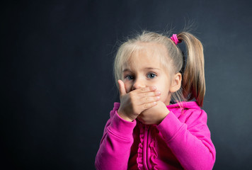 Little girl covers her mouth with hands