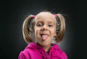 Beautiful little girl showing her tongue