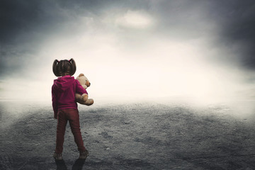 Little girl with toy bear in the darkness