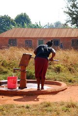 A woman and pump water from a public fountain-Pomerini-Tanzania-