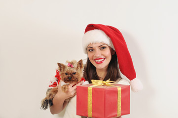 attractive happy woman in Santa hat with toy terrier and present