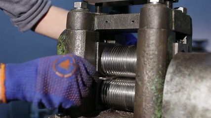 Craftsman rolling silver ingot in goldsmith