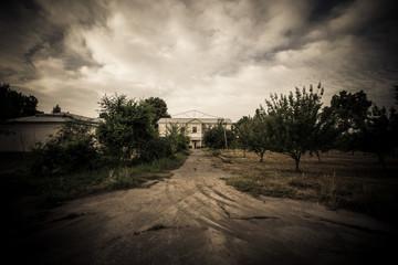 Dramatic road to house. Tajikistan. In dark colors