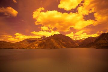 Expanse of Lake Iskander-Kul. Tajikistan. In orange tones