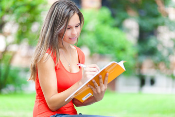 Female student reading a book at the park
