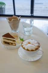 cup of cappuccino in a white cup with tiramisu cake on table