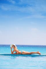 Beautiful woman with sunglasses lays on sea coast