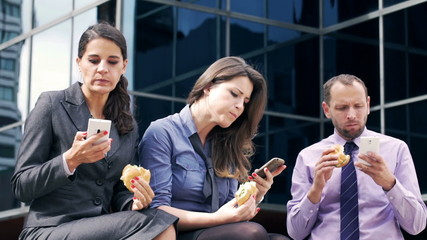 Businesspeople eating sandwiches and using cellphones