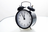 Oldfashioned black glossy alarm clock showing 5 to 12 poster