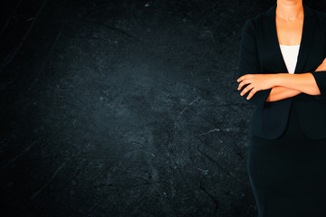 Close up of businesswoman with arms crossed against dark texture