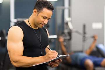 mid age male gym trainer writing on clipboard
