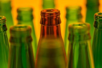 Ten Empty Beer Bottles Shot with Orange Light.