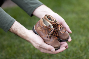 Dirty hands holding a pair of old childrens shoes