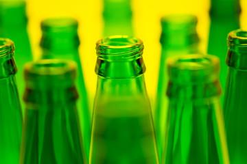 Ten Green Empty Beer Bottles Shot with Yellow Light.