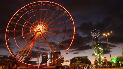 Ferris wheel rotates in the middle of the city at night