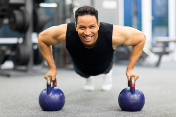 man doing pushup exercise with kettle bell