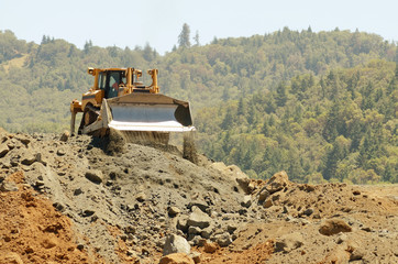Large bulldozer moving rock in a hill removal