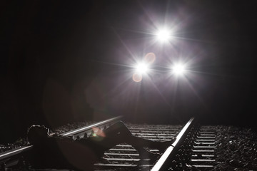 Woman lying on the railway tracks