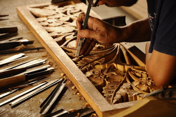 Skilled craftsman doing wood carving using traditional method