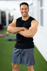 middle aged man with arms crossed in gym