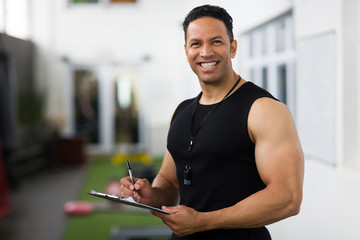 mid age trainer holding clipboard