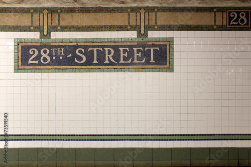 Plexiglas Treinstation New York City Station subway 28th Street sign on tile wall.