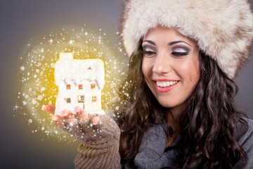 beautiful young woman in white hat holding magic house,Christmas
