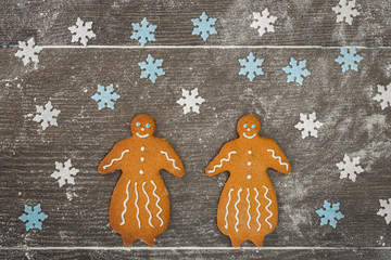 Two gingerbread ladies together on floury table.