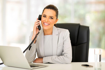 young businesswoman talking on landline phone