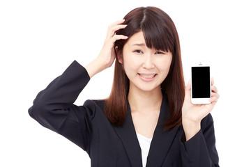 スマートフォンを見せて頭を抱えるビジネスウーマン