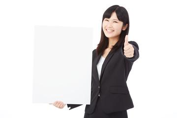 メッセージボードを持ってグッドサインするビジネスウーマン