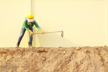 Laborer digging with hoe on construction site