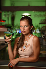 Pretty young brunette woman drinking cocktail in bar