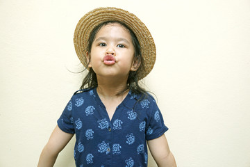 little girl with funny face and wear hat