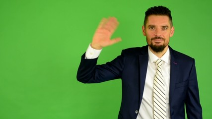 business man waving hand - green screen - studio