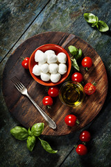 Cherry tomatoes, basil leaves, mozzarella cheese and olive oil f