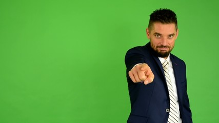 business man points to the camera - green screen - studio