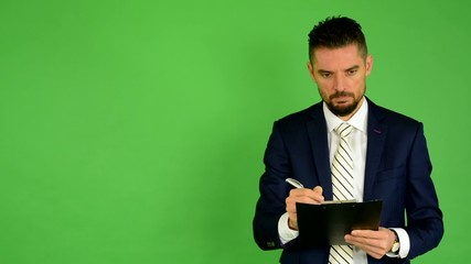 business man writes to paper (serious face) - green screen