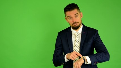 business man points to watch - green screen - studio