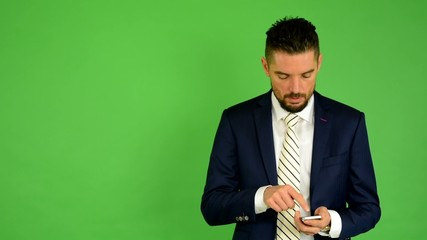 business man works on phone - green screen - studio