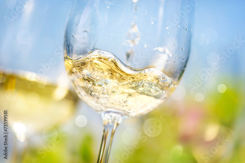 Pouring white wine in a glass - 73599581