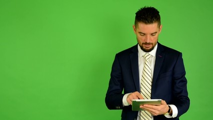 business man works on tablet and smiles - green screen