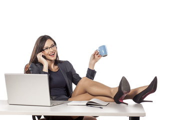 young businesswoman with legs on the table talking on the phone