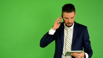 business man on the phone and works on tablet - green screen