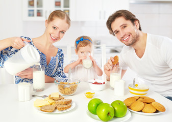 Happy family mother, father, child having breakfast