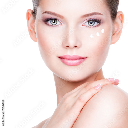 canvas print picture Young woman applying cream on her pretty face.