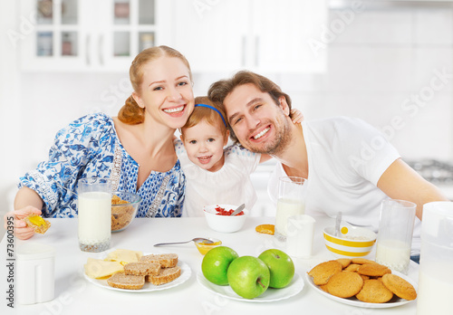 Happy family mother, father, child  having breakfast - 73600395