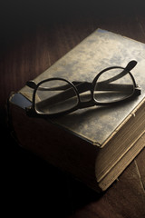 Eyeglasses on antique book.